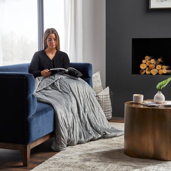 woman reading on sofa while using Malouf Anchor™ Weighted Throw Blanket