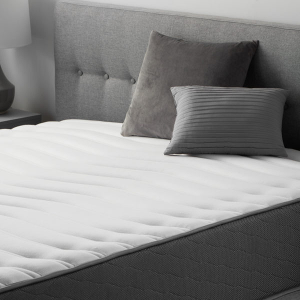 """side view of Neeva 12"""" Hybrid Mattress - Firm - in shown in a bedroom"""