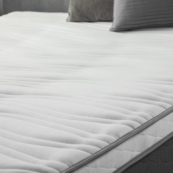 "side view of Neeva 12"" Hybrid Mattress - Plush - in shown in a bedroom"
